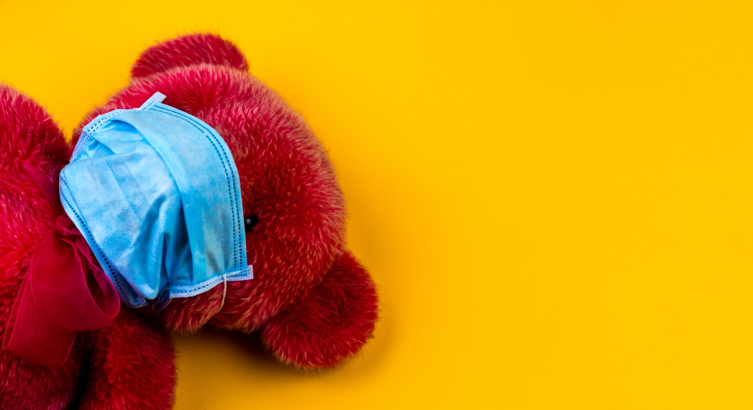 A child's bear with a mask on to prevent COVID -19 spread, test against a yellow background.